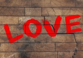 """Word """"Love"""" painted on old wooden wall background"""